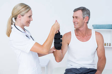 fractured: Doctor examining a man wrist in medical office Stock Photo