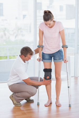Doctor examining his patient knee in medical office Stock Photo