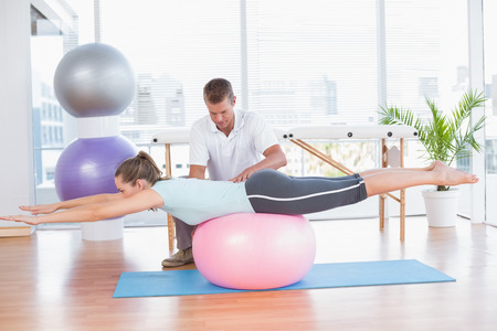 personal trainer: Trainer working with woman on exercise ball in fitness studio