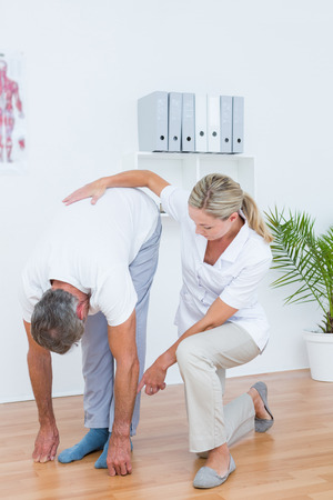 coccyx: Doctor examining her patient back in medical office