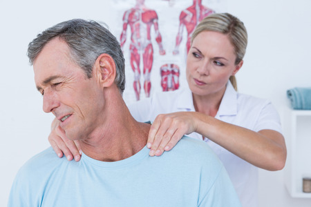 physiotherapy: Doctor stretching her patient neck in medical office