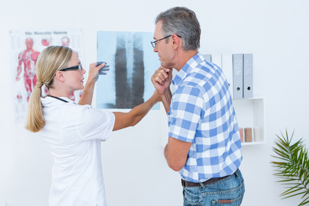 male chest: Doctor showing X rays to her patient in medical office Stock Photo