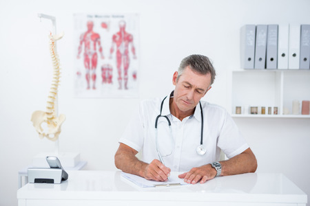 doctor writing: Doctor writing on clipboard at his desk in medical office