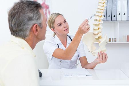 fisioterapia: Doctor que muestra su paciente un modelo de la columna vertebral en el consultorio médico