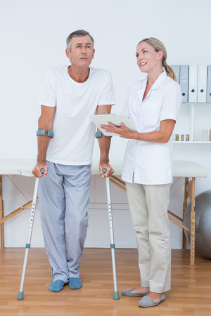 muscle retraining: Man with crutch speaking with his doctor in medical office Stock Photo