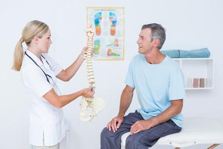 columna vertebral: Doctor que muestra la columna vertebral anat�mica a su paciente en el consultorio m�dico Foto de archivo