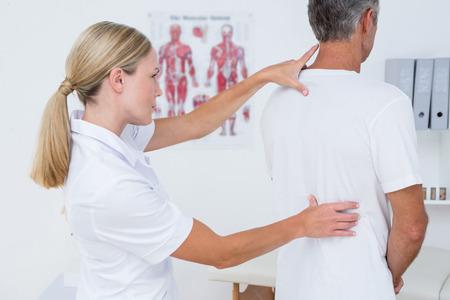 Arts de behandeling van haar patiënt terug in de medische kantoor