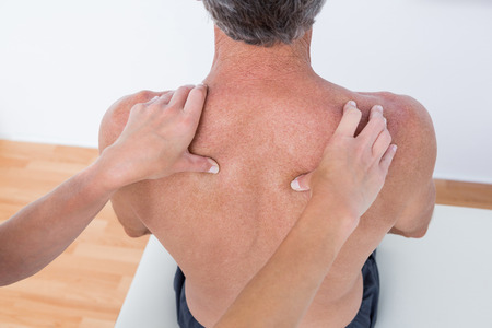 neuromuscular reeducation: Doctor examining his patient shoulder in medical office