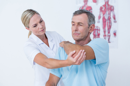 Doctor stretching a man arm in medical office Stock Photo