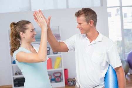 Woman celebrating with her trainer in fitness studio Stock Photo