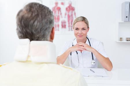 personas comunicandose: Doctor que mira la paciente que lleva cuello ortopédico en el consultorio médico