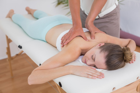 male massage: Physiotherapist doing back massage to his patient in medical office Stock Photo