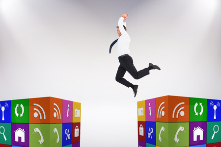 jumping businessman: Jumping businessman against grey background Stock Photo