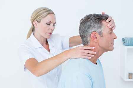 physical pressure: Doctor doing neck adjustment in medical office