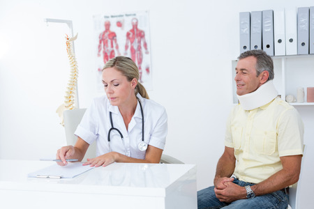 neck brace: Doctor examining her patient wearing neck brace in medical office