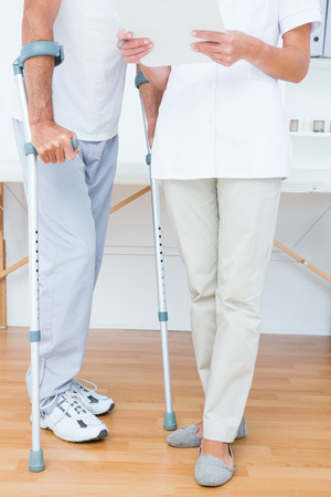 muscle retraining: Doctor showing clipboard to her patient with crutch in medical office