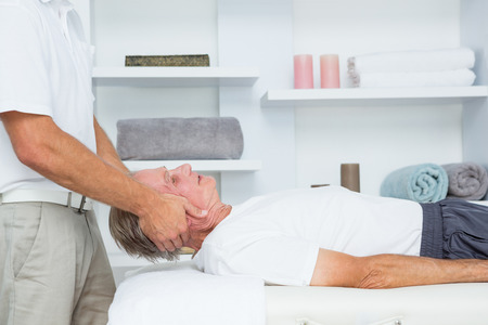 senior man on a neck pain: Man receiving neck massage in medical office