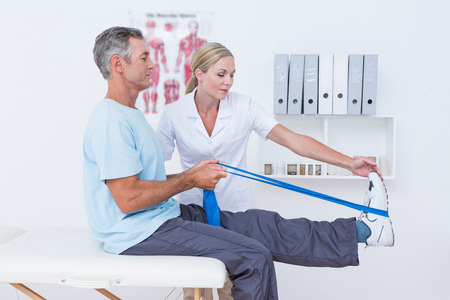 posture correction: Doctor examining her patient back legs in medical office