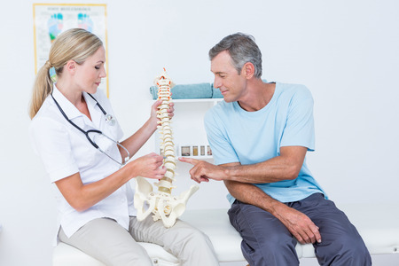 anatomical: Doctor showing anatomical spine to her patient in medical office