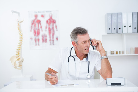 phoning: Doctor writing on clipboard and phoning in medical office