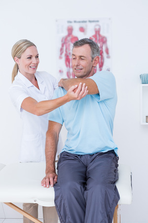 physical pressure: Doctor stretching a man arm in medical office Stock Photo