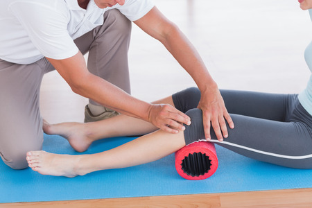 aiding: Trainer working with woman on exercise mat in fitness studio