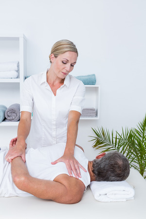 Physiotherapist doing shoulder massage to her patient in medical office Stock Photo