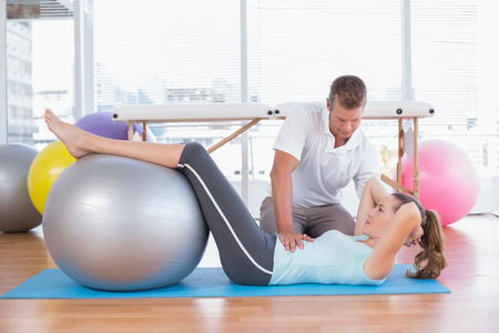 medical personal: Trainer working with woman on exercise mat in fitness studio