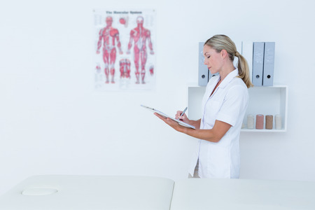 doctor writing: Doctor writing on clipboard in medical office Stock Photo