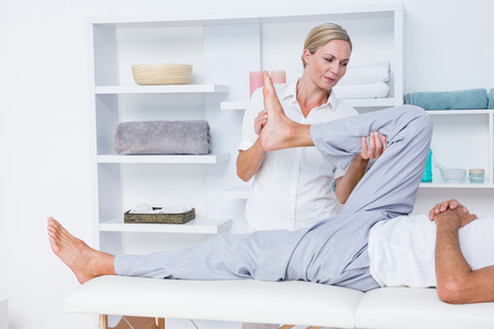 adult's feet: Physiotherapist doing leg massage to her patient in medical office Stock Photo