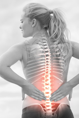 health concern: Digital composite of Highlighted spine of woman with back pain Stock Photo