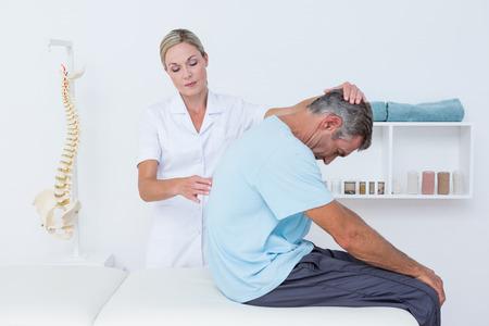 fisioterapia: El doctor se extiende a un hombre atrás en el consultorio médico