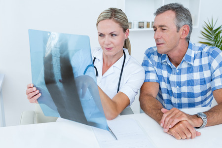 chest xray: Doctor showing X rays to her patient in medical office Stock Photo