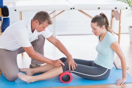 fisioterapia: Entrenador de trabajo con la mujer en la estera del ejercicio en gimnasio