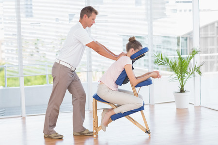 Donna che ha massaggio schiena in studio medico Archivio Fotografico - 42558038