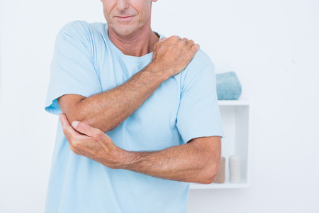 Man suffering from elbow pain in medical office Stock Photo