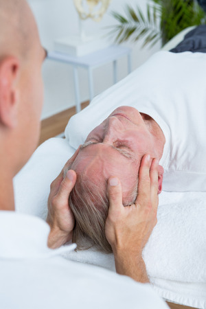 male massage: Man receiving head massage in medical office