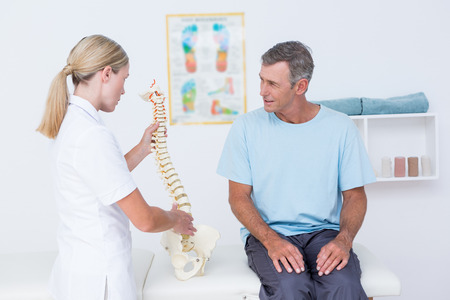 herniated: Doctor showing anatomical spine to her patient in medical office