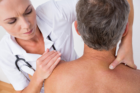 muscle retraining: Doctor examining her patient shoulder in medical office
