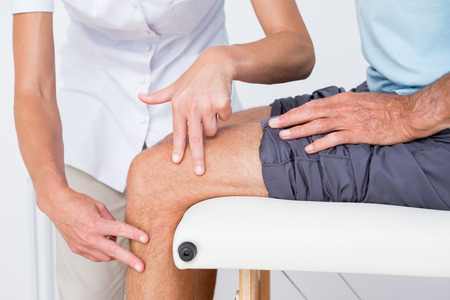 doctor care: Doctor examining her patient knee in medical office Stock Photo