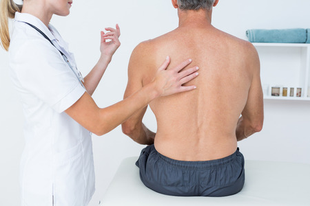 postural integration: Doctor examining her patient back in medical office