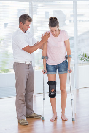 muscle retraining: Doctor helping his patient walking with crutch in medical office Stock Photo