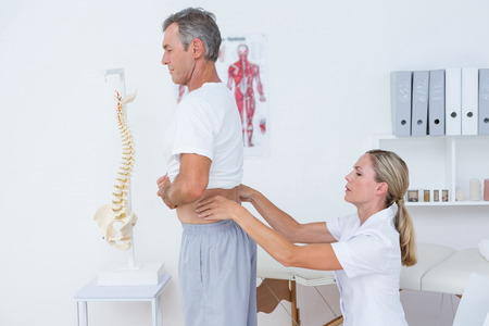 retraining: Doctor examining her patient back in medical office