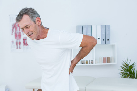 back ache: Suffering patient touching his back in medical office