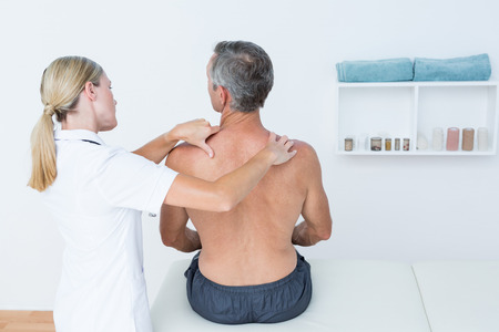 muscle retraining: Doctor examining her patient back in medical office