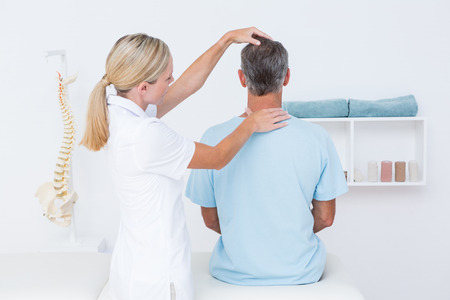 colonna vertebrale: Dottore facendo regolazione collo in ufficio medico