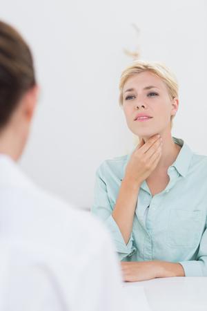 desolaci�n: Paciente con dolor de garganta doctor que visita en el consultorio m�dico