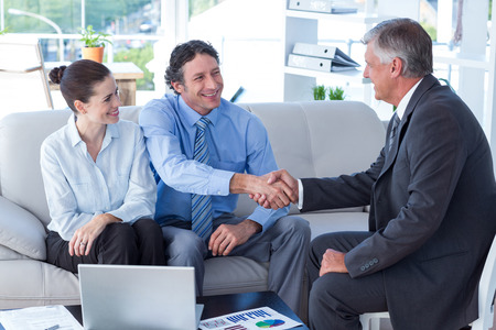 client meeting: Couple in meeting with a financial adviser in living room