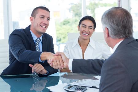 dando la mano: Socios de negocios dándose la mano en la oficina