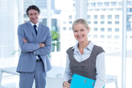 personas mirando: Hombres de negocios sonrientes mirando a la c�mara en una oficina